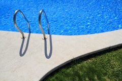 Blue tiles swimming pool with green grass garden royalty free stock photography