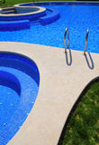 Blue tiles swimming pool with green grass garden royalty free stock images