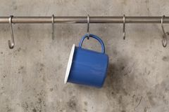 Free Blue Tin Cup Hanging On Stainless Rail On Cement Wall Background Royalty Free Stock Photo - 133648305