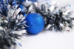 Blue tinsel and Christmas ball. Blue tinsel and blue Christmas ball on white background stock image