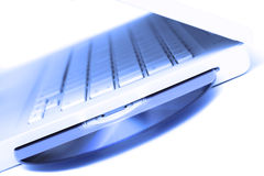 Blue tint white laptop with dvd disk in slot isola. White laptop with violet-blue color dvd disk in slot-loading drive Stock Photo