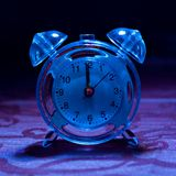 Blue Tinted Alarm Clock. A blue tinted alarm clock royalty free stock photos
