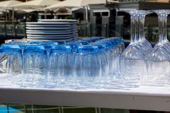 Blue tinted tumblers and wine glasses with plates stacked in a r royalty free stock images