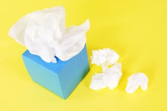 Kleenex style tissue box, yellow background, copy space. Tissues in blank blue box on a yellow background Royalty Free Stock Photo