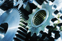 Blue titanium and steel gears. Large gear machinery against solid titanium and in a metal blue toning concept, one gear in blue toning Royalty Free Stock Images