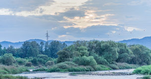 Blue tone landscape with a river running through countryside Royalty Free Stock Image
