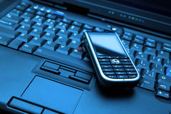 Blue-toned Connect. Keyboard of high-end laptop and modern smartphone on it. Tiff also available on demand. Blue-toned photo Stock Photos