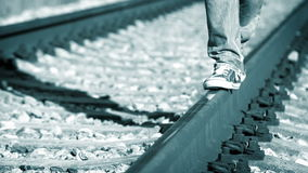 Blue-toned footage of a teenager goes along the railway in sneakers stock footage
