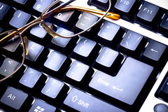 Blue toned keyboard with glasses Royalty Free Stock Images