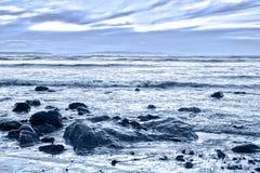 Blue toned rocky beal beach royalty free stock photos