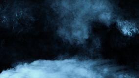 Blue toned . Rolling billows of smoke mist clouds from dry ice across the bottom light . Fog on floor isolated background stock photo