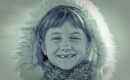 Blue toned square format image of young girl haired girl wearing Eskimo styled fur trimmed hood Stock Photo