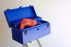 Blue toolbox and orange drill Royalty Free Stock Image