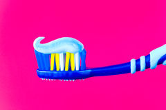 Blue toothbrush with blue toothpaste on a crimson background. Means of personal hygiene. Blue toothbrush with blue toothpaste on a crimson background stock images