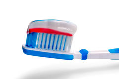 Blue toothbrush with tricolor toothpaste. Stock Images