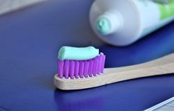 Blue toothpaste on a toothbrush. Blue toothpaste on purple stubble on wooden toothbrush stock photo