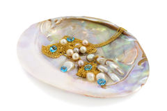 Blue topaz with pearls and gold. Blue topaz, pearl and gold chains in mother of pearl royalty free stock photos