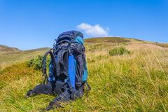 Touristic backpack among a green mountains. Blue touristic backpack among a green mountains Royalty Free Stock Photography