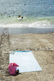 Blue towel. Beachwear standing in a concrete ramp by the sea Stock Photography