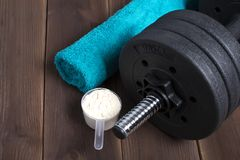Dumbbell and supplements on wooden floor. Fitness background with blue towel stock photography