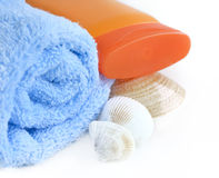 Blue towel with bottle of sunblock and sea shell Royalty Free Stock Photos
