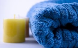 Blue towel and candles. Blue towel and two yellow candles Royalty Free Stock Images