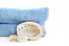 Blue towel and sea shell isolated on white Stock Images