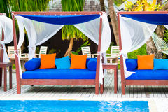 Blue towels on beach beds near swimming pool at Royalty Free Stock Photo