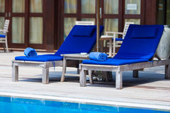 Blue towels on loungers near swimming pool at Stock Photography