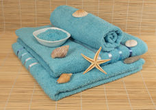 Blue towels with sea salt, shells, stones on bamboo Mat Royalty Free Stock Photo