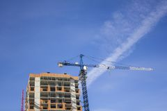 Blue tower crane near a tall building under construction on the background of a clear sky stock photos