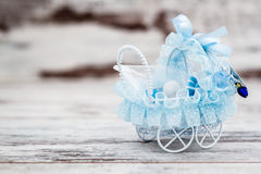 Blue Toy Baby Carriage Prepared as a Gift for Baby Shower. On white wooden background stock image
