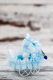 Blue Toy Baby Carriage Prepared as a Gift for Baby Shower. On white wooden background stock photos