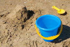 Blue toy bucket and yellow spade. Blue bucket and yellow spade on a beach Royalty Free Stock Images