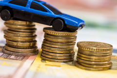 Blue toy car on coin and euro Royalty Free Stock Photo