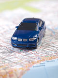 Blue toy car on a map. Blue toy car on a road map Royalty Free Stock Image