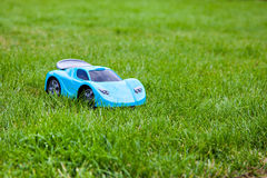 Blue toy sports car on green meadow Royalty Free Stock Photos
