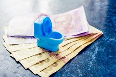 A blue toy toilet bowl stands on the money of Ukrainian hryvnas royalty free stock photo