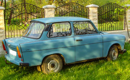 A blue trabant car. In the grass near a metal fence royalty free stock photos