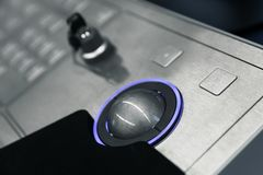 Blue trackball and security lock key. Industrial control panel made of gray metal with blue trackball and security lock key, close up photo with soft selective royalty free stock images