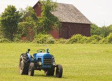 Blue Tractor. A blue tractor in a field and an overgrown barn in the distance Stock Image