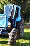 Blue tractor. Old blue tractor against green Royalty Free Stock Image