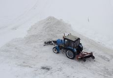 The blue tractor clears the snow stock image