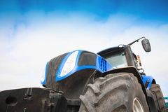Tractor close-up against the sky. Blue tractor close-up against the sky Royalty Free Stock Photography
