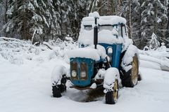 A blue tractor covered in snow. A blue tractor covered in white snow Royalty Free Stock Images