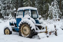 A blue tractor covered in snow. A blue tractor covered in white snow Royalty Free Stock Image