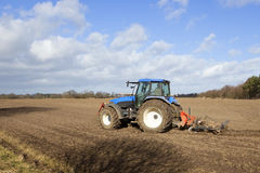 Blue tractor cultivating 2 Royalty Free Stock Photos