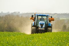Blue Tractor and fertilizer spreader in field Stock Photo