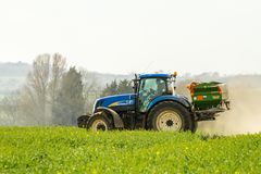 Blue Tractor and fertilizer spreader in field Royalty Free Stock Photography