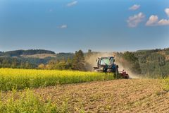 Blue tractor in a field of mustard in the Czech Republic. Dusty field and agricultural work. Autumn farm chores. Stock Photos